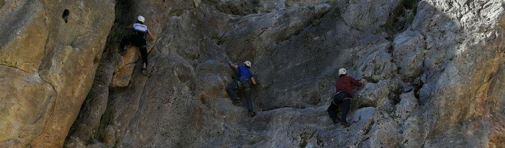 Fotografía de tres personas haciendo escalada en una montaña