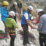 Un grupo prepara su equipo para comenzar una actividad de escalada