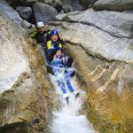 Varias personas lanzándose por un tobogán natural a una poza de agua en un barranco