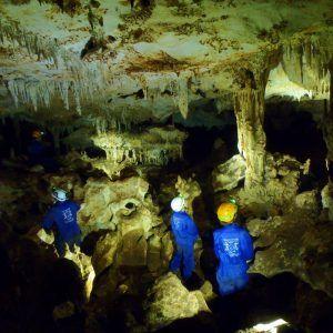 Un grupo de personas explorando una gruta mientras hacen espeleología