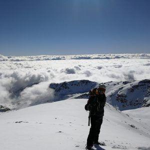 Una persona posa delante de un mar de nubes en la cima de la sierra