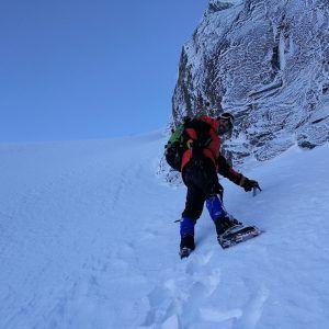 Una personas ascendiendo una montaña nevada