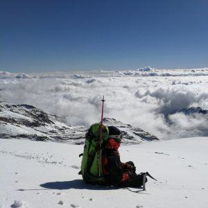 Una personas admirando las vistas desde la cima de la montaña