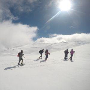 Un grupo de personas subiendo hacia la cima de la sierra con nieve densa