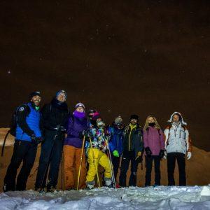 Varias personas de ruta en la sierra durante la luna llena