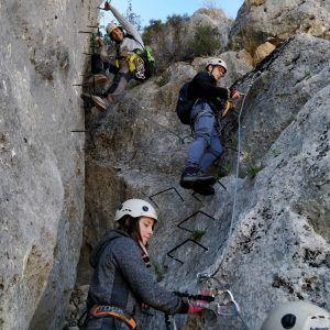 Varias personas subiendo una montaña a través de una vía ferrata en Moclín