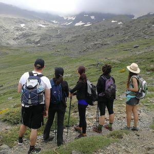 5 personas mirando la cima de la montaña mientras hacen senderismo